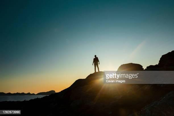 man silhouette over a rock at sunset - façanha imagens e fotografias de stock