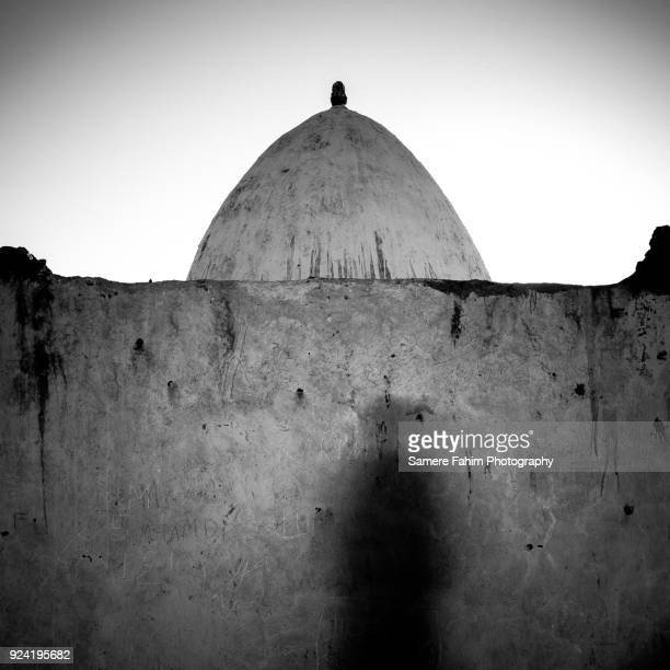 Man silhouette standing against a mausoleum