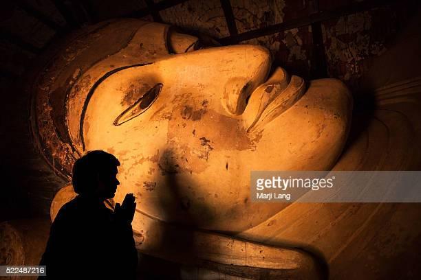 BAGAN MYANMAR BAGAN MYANMAR Man silhouette worshipping at the reclining Buddha statue in the Shinbinthalyaung temple in Bagan Myanmar The...