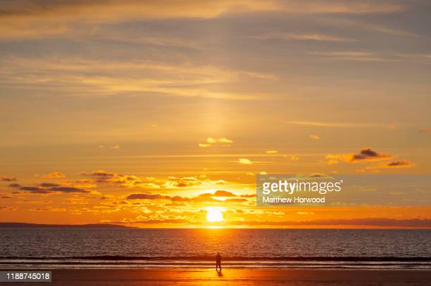 Man silhouetted by the sun during sunset at Southerndown beach on November 18, 2019 in Bridgend, United Kingdom.