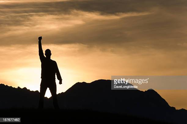 man silhouetted in front of mountain sunset - punching the air stock pictures, royalty-free photos & images