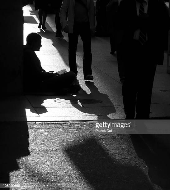 Man silhouetted in the afternoon light begs passers-by for spare change on a downtown street corner in Toronto, Ontario, Canada.