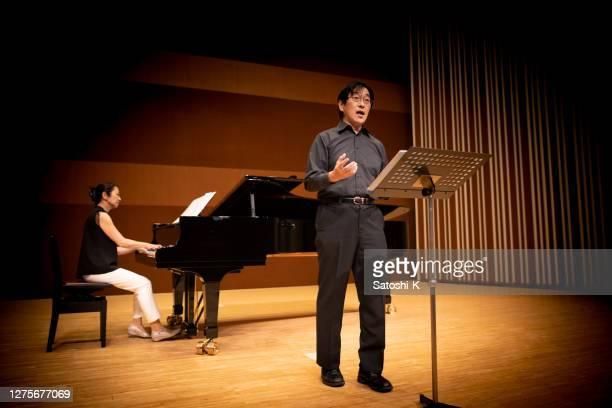 homme chantant une chanson au concert classique avec le piano - tranquil scene photos et images de collection