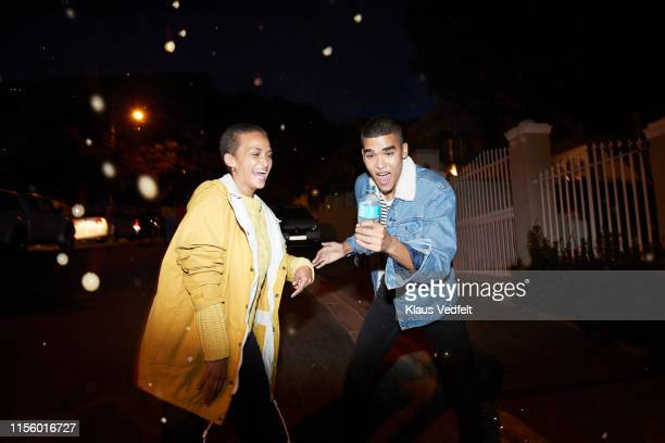 man singing and dancing with friend on street - girlfriend stock pictures, royalty-free photos & images