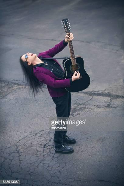 L'homme chantant et jouant de la guitare acoustique