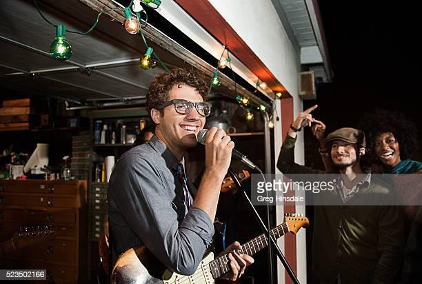 man singing at garage party - nur erwachsene stock-fotos und bilder