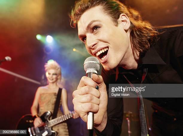 man singing into microphone by woman playing electric guitar - banda de rock - fotografias e filmes do acervo
