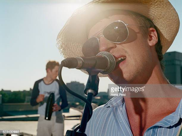 Man Singing into Microphone on Rooftop