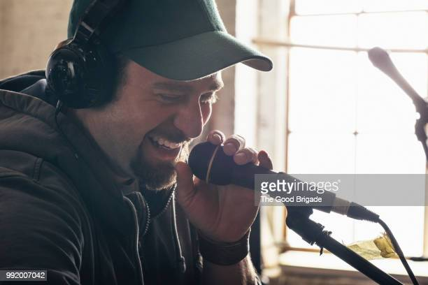 man singing while holding microphone in recording studio - recording studio stock pictures, royalty-free photos & images