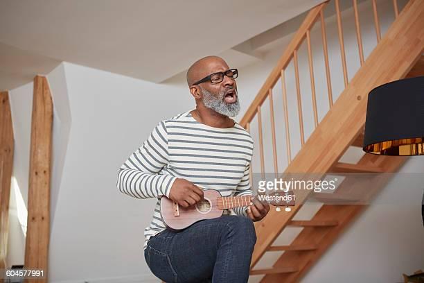 man singing while playing ukulele - ukulele stock pictures, royalty-free photos & images