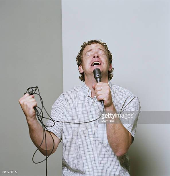 Man singing with passion into microphone