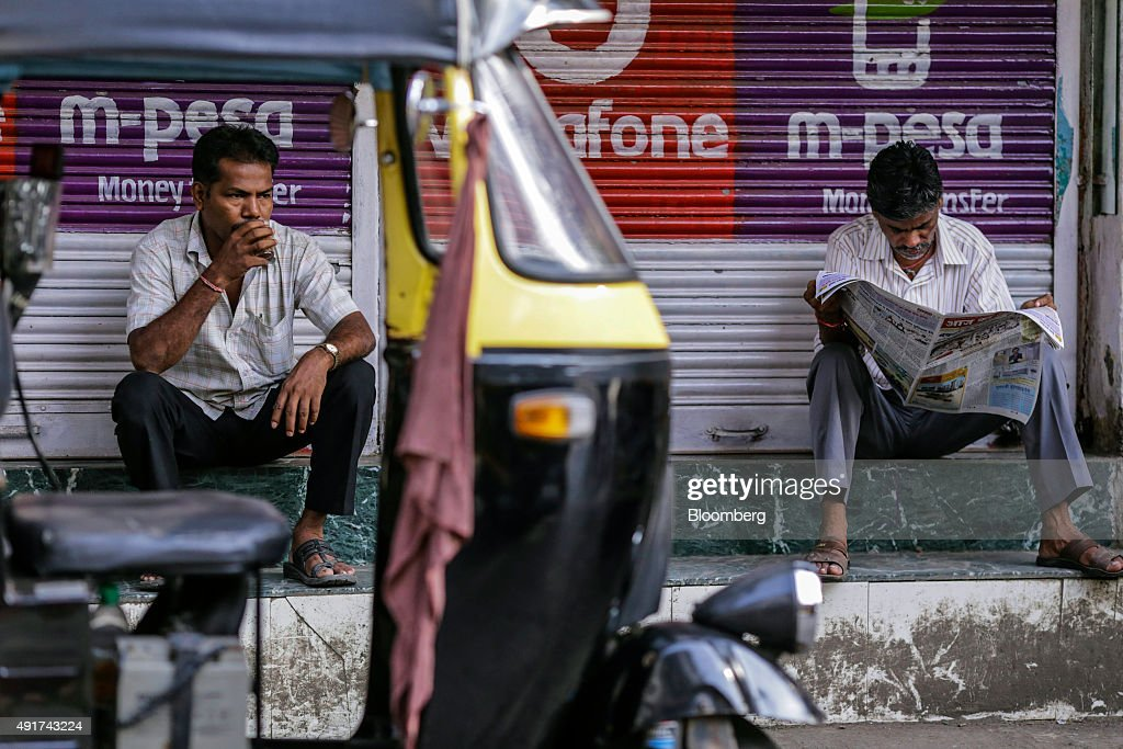 A man sips a glass of chai as another reads a newspaper in front of an auto-rickshaw in Mumbai, India, on Friday, Sept. 25, 2015. That sweet and milky tea concoction called chai is getting an image makeover in India. Rising incomes and demand for a refined experience transcending chai are spawning posh tea lounges in the nation's biggest cities. Photographer: Dhiraj Singh/Bloomberg via Getty Images