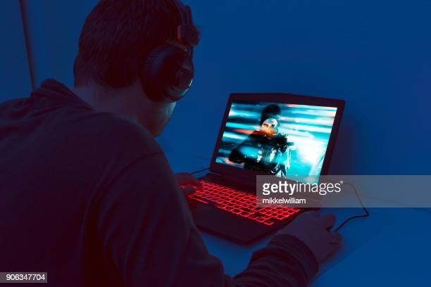 Mann allein vor Gaming-Laptop sitzen und spielt ein Videospiel