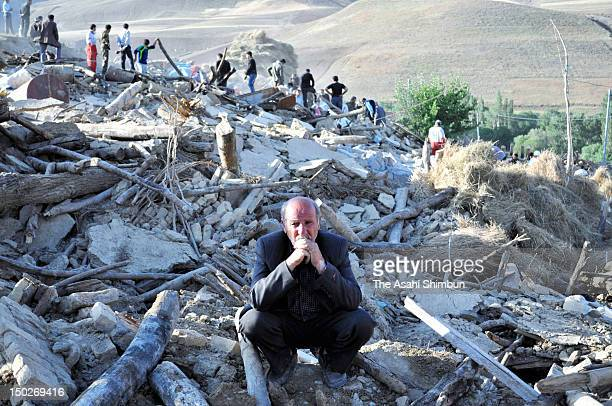 A man sit at the place where his house used to be on August 12 2012 in Varzaqan Iran The two earthquake within 11 minutes jolted northwestern Iran on...