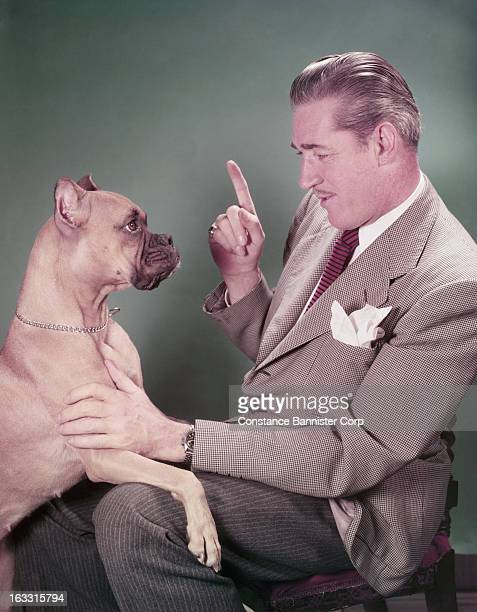 Man siting and pointing with boxer dog on his lap New York City USA
