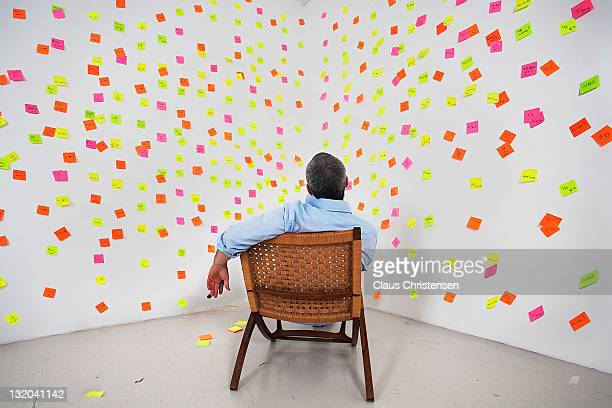 man siting in front of post it notes on the wall - strategie stockfoto's en -beelden