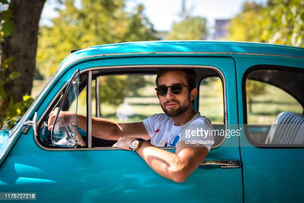 man siting in vintage car on the road - mediterranean culture stock pictures, royalty-free photos & images