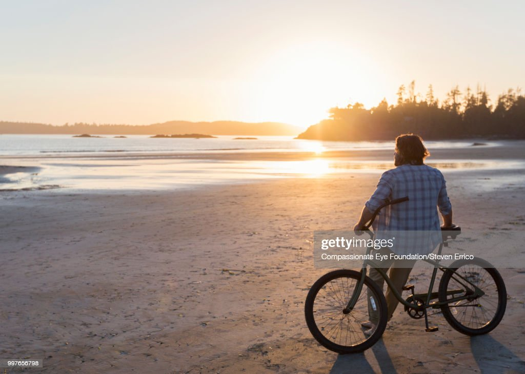Man siting on bike looking at ocean view at sunset : Stock Photo