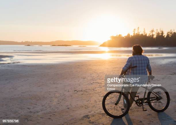 """man siting on bike looking at ocean view at sunset - """"compassionate eye"""" stock pictures, royalty-free photos & images"""