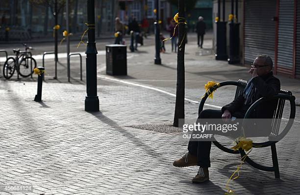 A man sits adjacent amongst yellow ribbons tied to street furniture for murdered aid worker Alan Henning in Eccles north west England on October 5...