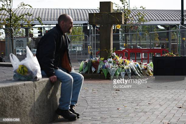 A man sits adjacent to the floral tributes at the base of the Eccles Cross for murdered aid worker Alan Henning in Eccles north west England on...