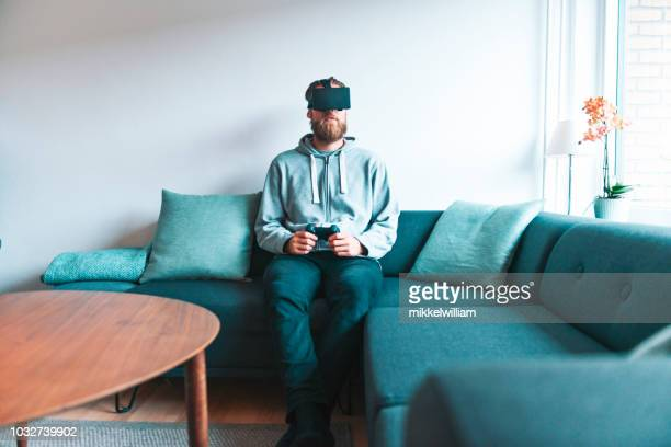 Man sits alone in living room and play virtual reality video game