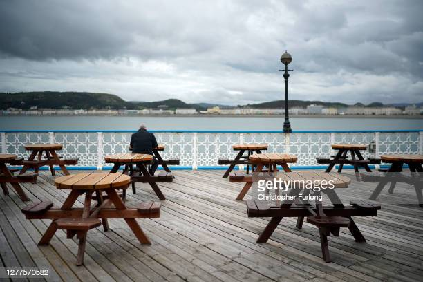 Man sits alone on Llandudno Pier before new Covid-19 regulations come into effect on September 30, 2020 in Llandudno, United Kingdom. New local...