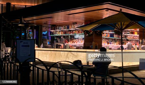 Man sits alone with his drink near the bar as people visit Disneyland where parts of the park opened today for more retail and dining as an extension...