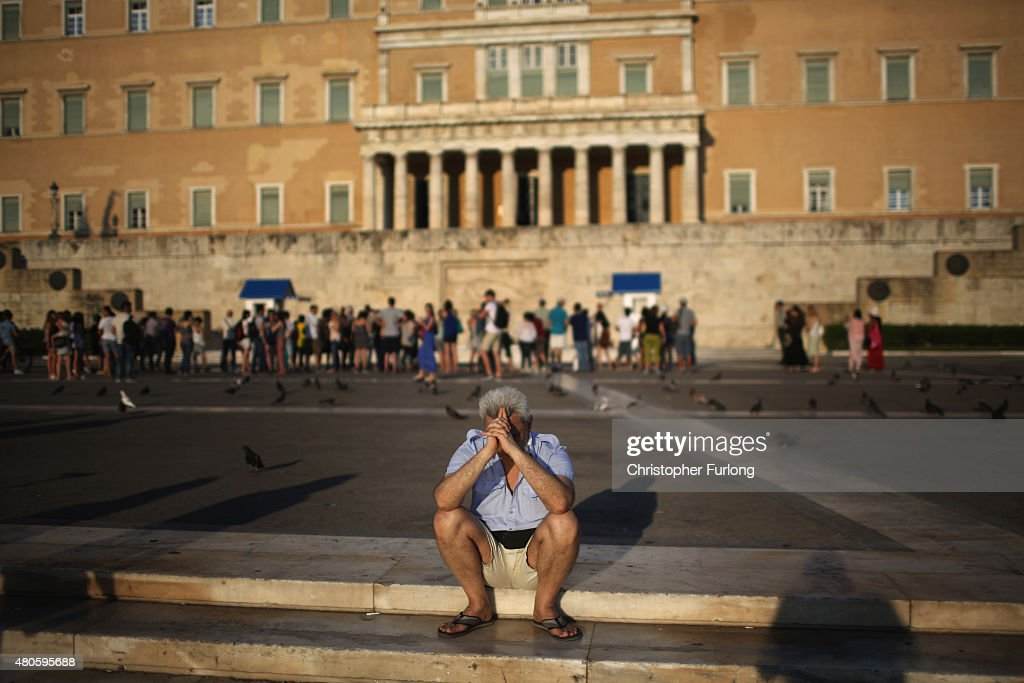 A man sits alone with his thoughts as protesters gather outside the Greek parliament to demonstrate against austerity after an agreement for a third bailout with eurozone leaders on July 13, 2015 in Athens, Greece. The bailout is conditional on Greece passing agreed reforms in parliament by Wednesday which includes streamlining pensions and rasing more raise tax revenue.