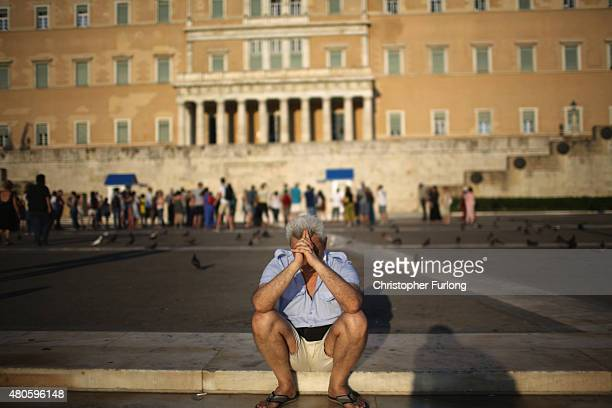 Man sits alone with his thoughts as protesters gather outside the Greek parliament to demonstrate against austerity after an agreement for a third...