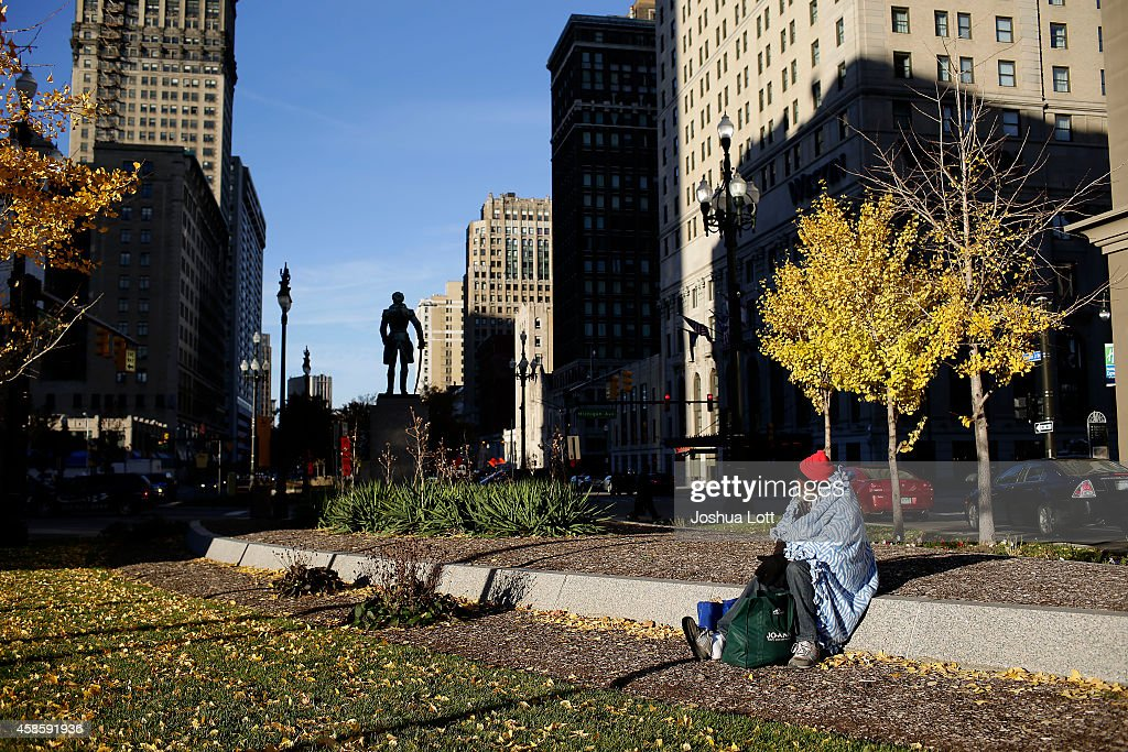A man sits along Washington Boulevard November 7, 2014 in Detroit, Michigan. Today U.S. Bankruptcy Judge Steven Rhodes gave the City of Detroit the okay to plan an exit strategy from Chapter 9 Bankruptcy.