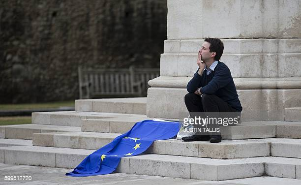 A man sits alongside a European Union flag outside the Houses of Parliament before the British government ahead of a House of Commons debate on a...