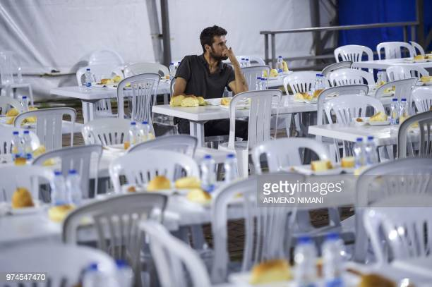 A man sits amid empty chairs as he receives free Iftar meal to break the fast during the last day of the Muslim holy month of Ramadan on June 14 2018...
