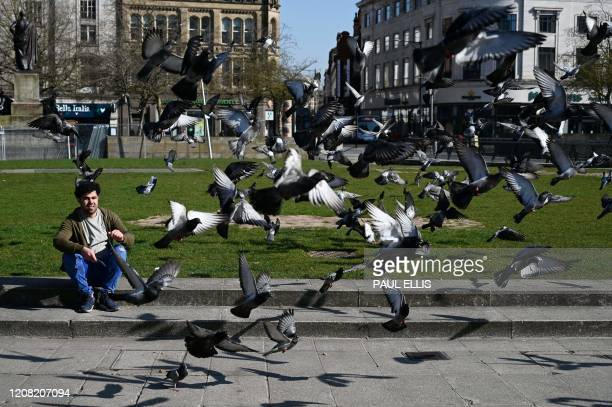 A man sits amongst pigeons in Manchester north west England on March 25 after Britain's government ordered a lockdown to slow the spread of the novel...