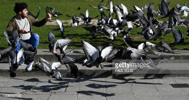 TOPSHOT A man sits amongst pigeons in Manchester north west England on March 25 2020 after Britain's government ordered a lockdown to slow the spread...