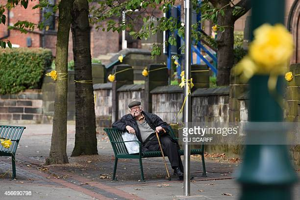 A man sits amongst yellow ribbons tied to street furniture for murdered aid worker Alan Henning in Eccles north west England on October 5 2014...