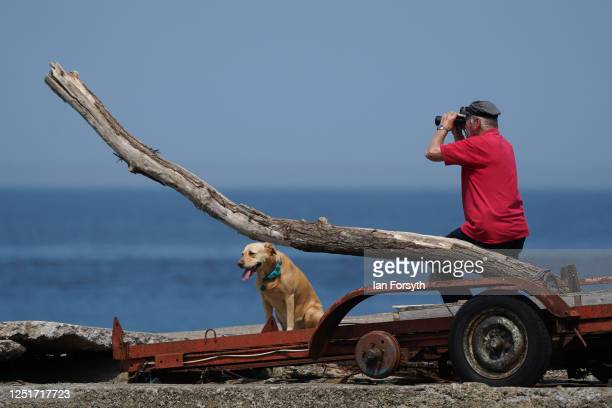 Man sits and looks through binoculars at South Gare near Redcar as people enjoy the hot weather on June 24, 2020 in Redcar, United Kingdom. A summer...