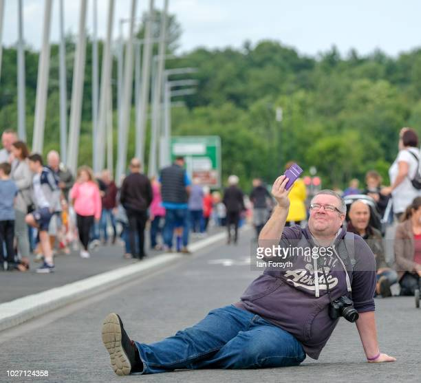 A man sits and takes a photograph on the new Northern Spire bridge spanning the River Wear as it opens for a pedestrian walkover on August 28 2018 in...