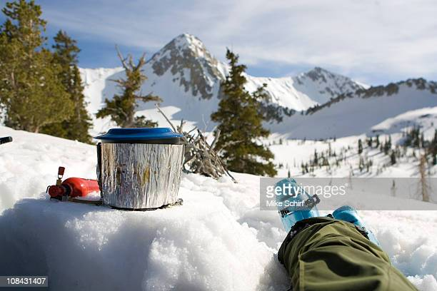A man sits and waits for his water to boil while enjoying the view.