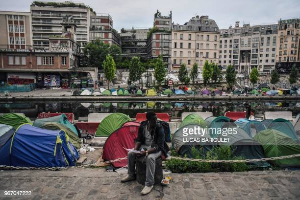 TOPSHOT A man sits as migrants prepare their belongings at the start of the evacuation by police of their makeshift camp along the Canal de...
