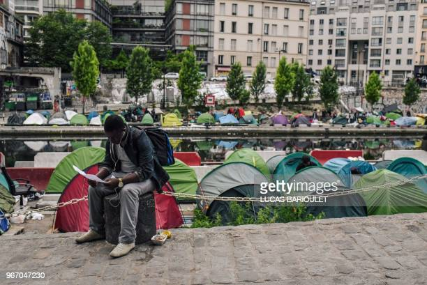A man sits as migrants prepare their belongings at the start of the evacuation by police of their makeshift camp along the Canal de SaintMartin at...
