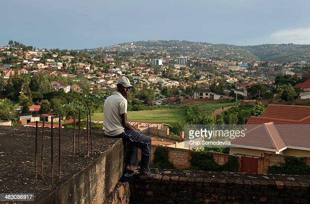 A man sits as the evening sun falls over the Kicukiro District of the capital April 5 2014 in Kigali Rwanda Built in hilly country in the heart of...