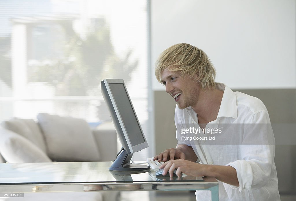 Man Sits at a Glass Table Using His Computer : Stock Photo