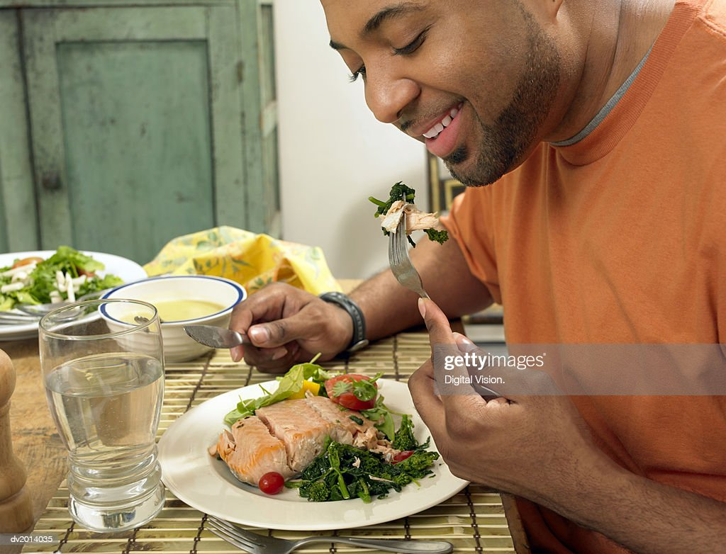 Man Sits at a Table at Home Eating a Salmon Salad for Lunch : Stock Photo