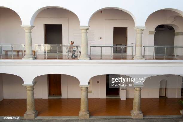 A man sits at a table in the Museo de Arte Contemporaneo de Oaxaca / Oaxaca Museum of Contemporary Art in the Casa de Cortes Oaxaca is known...