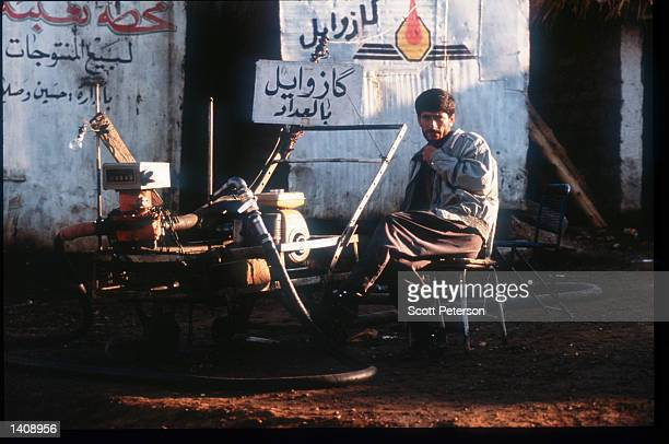 A man sits at a truck stop where Iraqi oil is sold in violation of the UN embargo April 16 1996 in Dahuk Iraq Efforts by the Kurds to achieve...