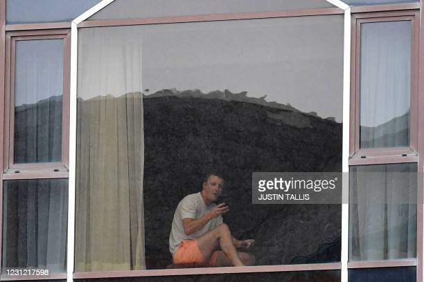 Man sits at a window of the Radisson Blu hotel at Heathrow Airport in west London on February 17, 2021 where travellers are undertaking mandatory...