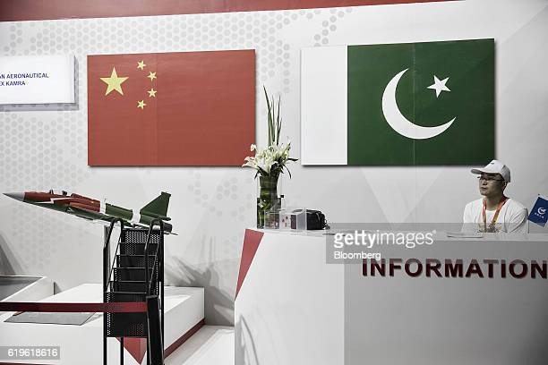 A man sits at an information counter next to a model of Aviation Industry Corp of China's FC1 multipurpose fighter aircraft and the flags of China...
