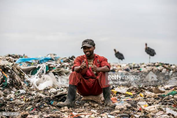 A man sits at the Dandora rubbish dump on March 14 2018 in Nairobi Kenya The Dandora landfield is located 8 Kilometer east of the city center of...