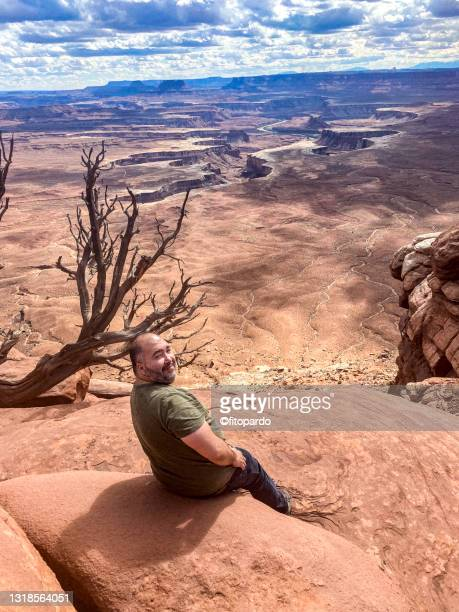 a man sits at the edge of the canyon at canyonlands national park - fitopardo stock pictures, royalty-free photos & images